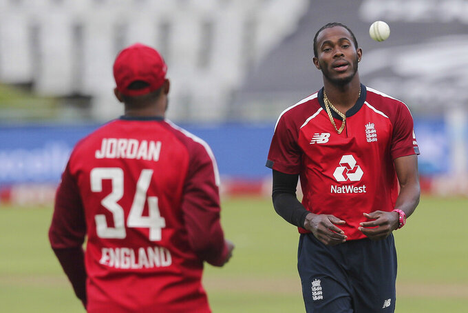 Jofra Archer receives the ball from Chris Jordan between bowls during the third T20 cricket match between South Africa and England in Cape Town, South Africa, Sunday, Nov. 29, 2020. (AP Photo/Halden Krog)