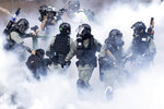 In this Monday, Nov. 18, 2019, file photo, police in riot gear move through a cloud of smoke as they detain a protester at the Hong Kong Polytechnic University in Hong Kong. Hong Kong police fought off protesters with tear gas and batons Monday as they tried to break through a police cordon that is trapping hundreds of them on a university campus. (AP Photo/Ng Han Guan, File)