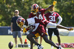 Washington Redskins cornerback Josh Norman (24) breaks up a pass intended for wide receiver Brian Quick (83) during the first day of NFL football training camp in Richmond, Va., Thursday, July 25, 2019. (AP Photo/Steve Helber)