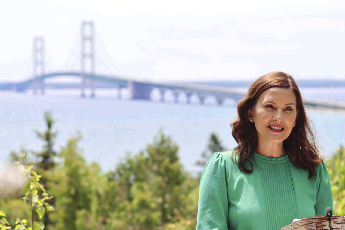 FILE - In this June 10, 2021 file photo provided by the Michigan Office of the Governor, Gov. Gretchen Whitmer speaks at Straits State Park in St. Ignace, Mich., with the Mackinac Bridge behind her. Michigan will lift all indoor capacity restrictions and mask requirements next week, 10 days sooner than planned amid vaccinations and plummeting COVID-19 infections, Whitmer announced Thursday, June 17. (Michigan Office of the Governor via AP, File)