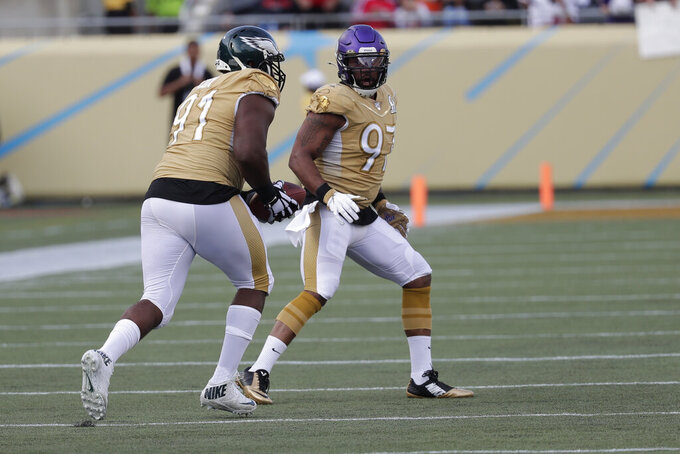 NFC defensive end Fletcher Cox, of the Philadelphia Eagles, runs for a touchdown, after an interception by strong safety Harrison Smith, of the Minnesota Vikings, (22), during the second half of the NFL Pro Bowl football game against the AFC, Sunday, Jan. 26, 2020, in Orlando, Fla. To the right is defensive end Everson Griffen, of the Minnesota Vikings (97). (AP Photo/John Raoux)