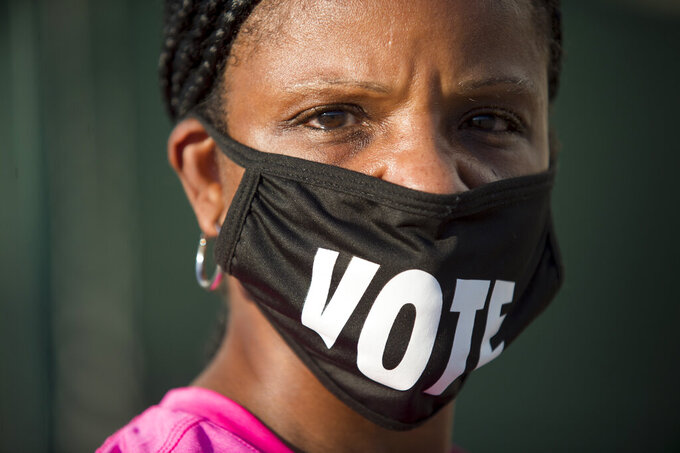 """FILE - In this Oct. 26, 2020, file photo, Caprice Clipps wears a """"vote"""" mask as she waits outside the Smoothie King Center in New Orleans for one of the last days of early voting. Several years since its founding, BLM has evolved well beyond the initial aspirations of its early supporters. Now, its influence faces a test, as voters in the Tuesday, Nov. 3 general election choose or reject candidates who endorsed or denounced the BLM movement amid a national reckoning on race. (Chris Granger/The Advocate via AP, File)"""