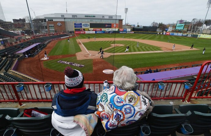 FILE - In this April 18, 2018, file photo, Debbie McCracken, left, and Ted Grimm, both of Millcreek Township, watch the Erie SeaWolves play the Trenton Thunder in the opening game of a Double-A baseball doubleheader in Erie, Pa. Major League Baseball is pushing a proposal to whack 42 teams _ and several entire leagues _ from its vast network of minor-league affiliates that bring the game to every corner of country. (Jack Hanrahan/Erie Times-News via AP, File)