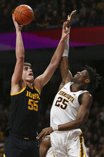 Iowa's Luka Garza, left, shoots against Minnesota's Daniel Oturu during the second half of an NCAA college basketball game Sunday, Feb. 16, 2020, in Minneapolis. (AP Photo/Stacy Bengs)