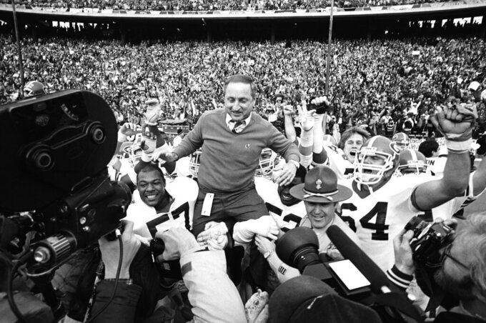FILE - In this Jan. 2, 1984, file photo, Georgia coach Vince Dooley is carried off the field after Georgia beat Texas 10-9 in the Cotton Bowl in Dallas. Georgia is planning to honor Hall of Fame former coach Vince Dooley by naming the field at Sanford Stadium in his honor. A ceremony has been planned for Georgia's 2019 opening game on Sept. 7 against Murray State to dedicate Dooley Field at Sanford Stadium. (AP Photo/Paul Moseley, File)