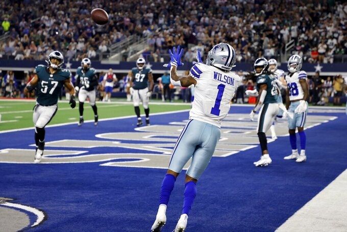 Dallas Cowboys wide receiver Cedrick Wilson (1) reaches up to catch a touchdown pass as Philadelphia Eagles linebacker T.J. Edwards (57) and others look on in the second half of an NFL football game in Arlington, Texas, Monday, Sept. 27, 2021. (AP Photo/Ron Jenkins)