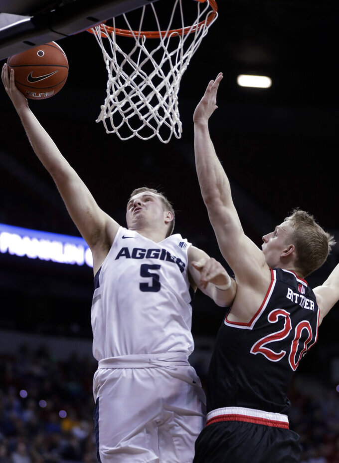 Utah State's Sam Merrill (5) shoots as Fresno State's Sam Bittner defends during the first half of an NCAA college basketball game in the Mountain West Conference men's tournament Friday, March 15, 2019, in Las Vegas. (AP Photo/Isaac Brekken)