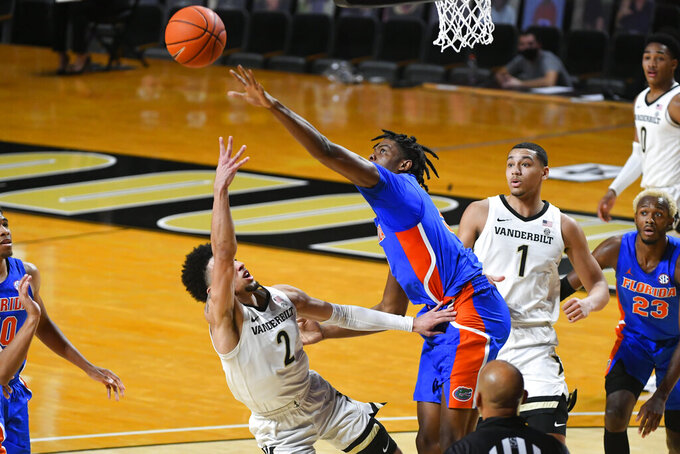 Florida forward Omar Payne blocks a shot by Vanderbilt guard Scotty Pippen Jr. (2) during the first half of an NCAA college basketball game Wednesday, Dec. 30, 2020, in Nashville, Tenn. (AP Photo/John Amis)