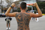 A Barcelona fan poses showing tattoos of Lionel Messi and other Barcelona players before FC Barcelona club President Joan Laporta gives a news conference in Barcelona, Spain, Friday, Aug. 6, 2021. Barcelona announced on Thursday Aug. 5, 2021 that Messi will not stay with the club. He is leaving after 17 successful seasons in which he propelled the Catalan club to glory, helping it win numerous domestic and international titles since debuting as a teenager. (AP Photo/Joan Monfort)