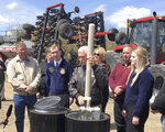 Vice President Mike Pence, center, holds a tube of soy beans as he tours the R & J Johnson Farms in Glyndon, Minn., Thursday, May 9, 2019, to talk about the Trump administration's trade agreement with Canada and Mexico. Famers who visited with Pence emphasized the importance of selling soy beans as Minnesota ranks third among all states in soy bean production. (AP Photo/Dave Kolpack)