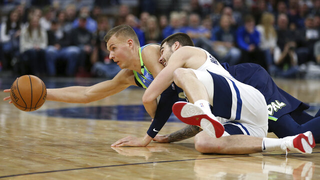 Dallas Mavericks' Kristaps Porzingis reaches out for a loose ball against Minnesota Timberwolves' Juancho Hernangomez in the second half of an NBA basketball game Sunday, March 1, 2020, in Minneapolis. Dallas won 111-91. (AP Photo/Stacy Bengs)
