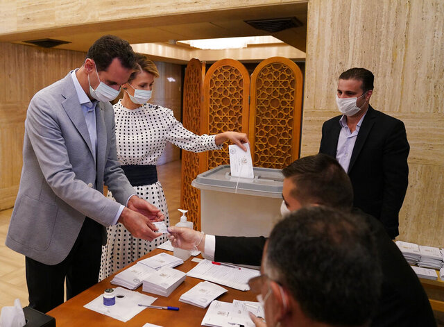 In this photo released on the official Facebook page of Syrian Presidency, Syrian President Bashar Assad and his wife Asma vote at a polling station in the parliamentary elections in Damascus, Syria, Sunday, July 19, 2020. Syrians headed to polling stations in government-held parts of the war-torn country on Sunday to elect a new parliament amid strict health measures to prevent the spread of coronavirus amid an increase of cases in recent days. (Syrian Presidency via AP)