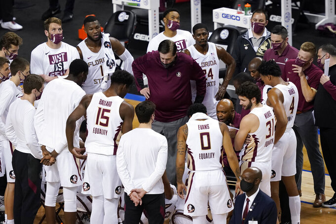 Florida State head coach Leonard Hamilton, seated center right, talks to his team during the first half of an NCAA college basketball game in the semifinal round of the Atlantic Coast Conference tournament in Greensboro, N.C., Friday, March 12, 2021. (AP Photo/Gerry Broome)