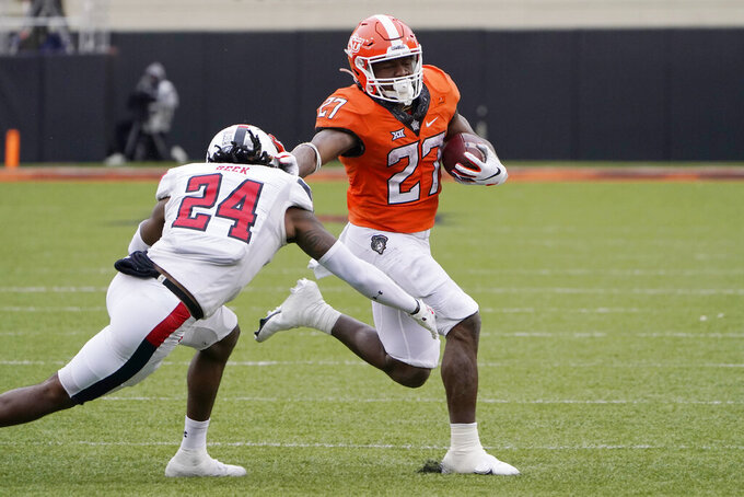 Oklahoma State running back Dezmon Jackson (27) carries past Texas Tech defensive back Adam Beck (24) in the second half of an NCAA college football game in Stillwater, Okla., Saturday, Nov. 28, 2020. (AP Photo/Sue Ogrocki)