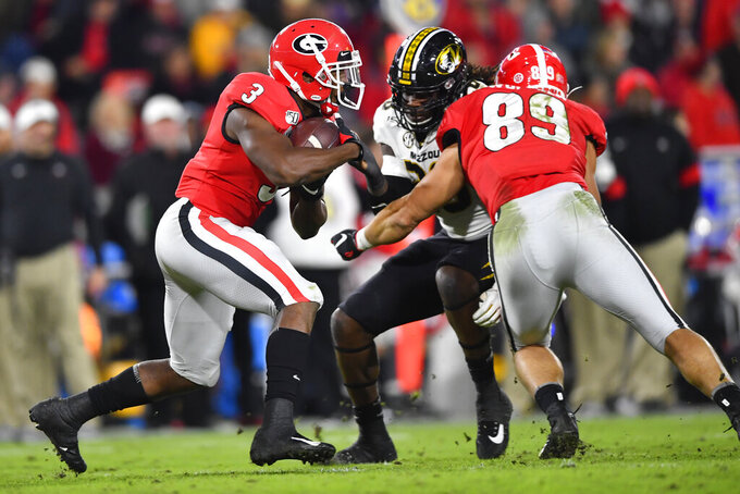 Georgia running back Zamir White (3) rushes as Georgia tight end Charlie Woerner (89) blocks Missouri linebacker Nick Bolton during the first half of an NCAA college football game Saturday, Nov. 9, 2019, in Athens, Ga. (AP Photo/John Amis)