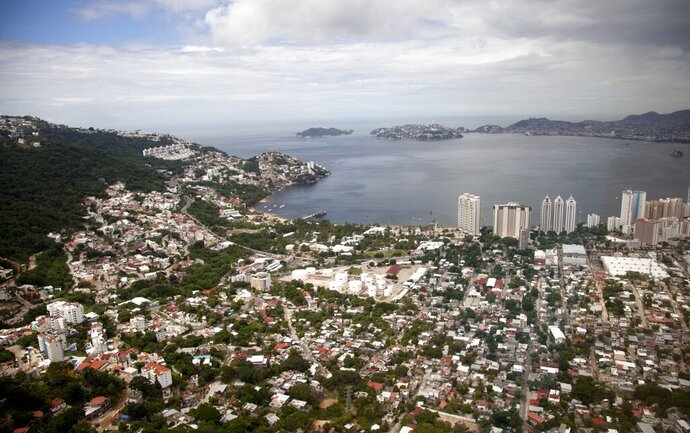 "FILE - This Sept. 20, 2013 file photo shows an aerial view of the Pacific resort city of Acapulco, Mexico. The Mexican coastal city pulled a pair of controversial video ads Thursday, Aug. 6, 2020, touting the faded resort's reputation as an ""anything goes"" tourism destination because they weren't appropriate during the new coronavirus pandemic. (AP Photo/Eduardo Verdugo, File)"