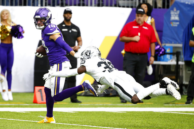 Minnesota Vikings wide receiver Adam Thielen breaks a tackle by Oakland Raiders free safety Curtis Riley, right, during a 35-yard touchdown reception in the first half of an NFL football game, Sunday, Sept. 22, 2019, in Minneapolis. (AP Photo/Bruce Kluckhohn)