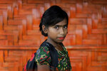 In this June 27, 2018, photo, Taslima, 10, poses for a portrait in front of her classroom in Chakmarkul refugee camp, Bangladesh. Amid the misery and mud of Bangladesh's refugee camps, Rohingya girls have found small moments of joy by adorning themselves with flowery headbands and elaborately-drawn makeup. (AP Photo/Wong Maye-E)