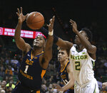 FILE - In this Feb. 23, 2019, file photo, West Virginia forward Derek Culver, left, reaches past Baylor guard Devonte Bandoo, right, for a loose ball in the first half of an NCAA college basketball game, in Waco, Texas. Culver became the Big 12's top rebounder in conference play last season after missing the first 10 games for an undisclosed violation of team rules.  (Rod Aydelotte/Waco Tribune-Herald via AP, File)