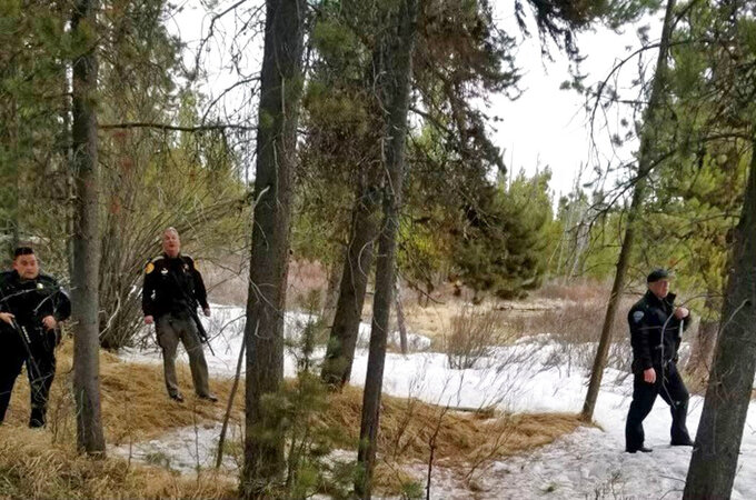 """In this photo provided by the Gallatin County Sheriff's Office, officers from the sheriff's office and West Yellowstone Police Department are seen near the scene of a grizzly bear mauling just outside Yellowstone National Park near West Yellowstone, Mont. on April, 15, 2021. Authorities said Charles """"Carl"""" Mock died Saturday of injuries sustained in the attack. (Gallatin County Sheriff's Office via AP)"""