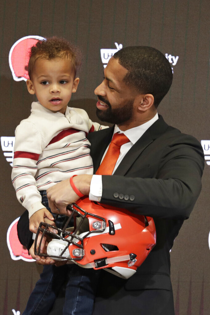 Cleveland Browns general manager Andrew Berry holds his two-year old son, Zion, after speaking at a news conference at the NFL football team's training facility, Wednesday, Feb. 5, 2020, in Berea, Ohio. Berry returned to the team after a one-year stint in the Philadelphia Eagles' front office. Berry was the Browns' vice president of player personnel from 2016-18. (AP Photo/Tony Dejak)