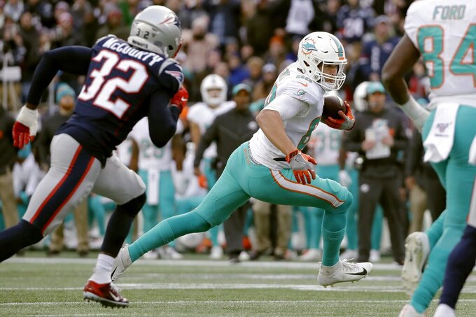 Miami Dolphins tight end Mike Gesicki runs from New England Patriots safety Devin McCourty, left, after catching a pass in the second half of an NFL football game, Sunday, Dec. 29, 2019, in Foxborough, Mass. (AP Photo/Elise Amendola)