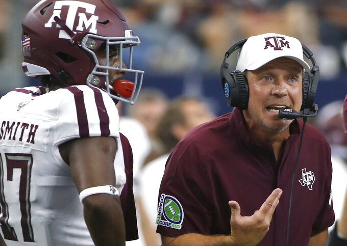 Texas A&M head coach Jimbo Fisher talks with his team as wide receiver Ainias Smith (17) looks on as they play Arkansas during the first half of an NCAA college football game Saturday, Sept. 28, 2019, in Arlington, Texas. Texas A&M won 31-27. (AP Photo/Ron Jenkins)