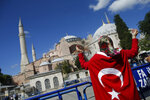 FILE - In this Friday, July 10, 2020, file photo, a woman, draped in a Turkish flag, chants slogans, outside the Byzantine-era Hagia Sophia, one of Istanbul's main tourist attractions in the historic Sultanahmet district of Istanbul, following Turkey's Council of State's decision that paved the way for the landmark monument to be turned from a museum into a mosque. Turkish President Recep Tayyip Erdogan is scheduled to join hundreds of worshipers Friday, July 24, for the first Muslim prayers at the Hagia Sophia in 86 years. (AP Photo/Emrah Gurel, File)