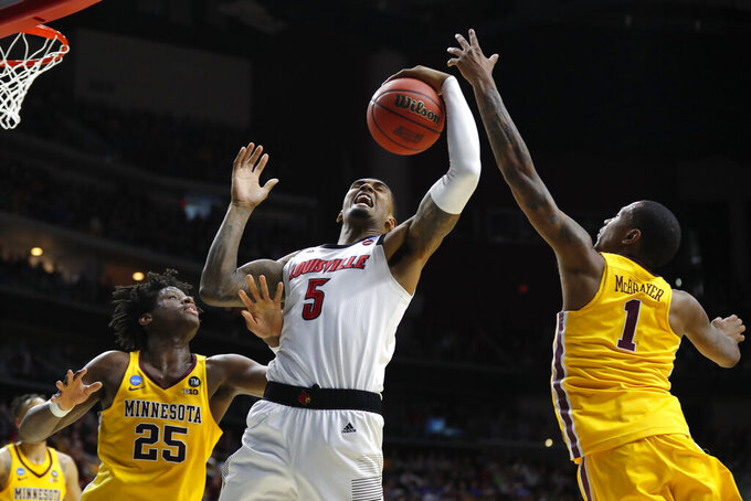 Louisville center Malik Williams (5) fights for a rebound with Minnesota's Daniel Oturu, left, and Dupree McBrayer, right, during a first round men's college basketball game in the NCAA Tournament, Thursday, March 21, 2019, in Des Moines, Iowa. (AP Photo/Charlie Neibergall)