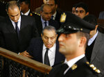 Former Egyptian President Hosni Mubarak, center, arrives with his sons Alaa, left, and Gamal, right, to testify, in a courtroom at the National Police Academy in Cairo, Egypt, Wednesday, Dec. 26, 2018. Two former Egyptian presidents appeared Wednesday in the same Cairo courtroom, with Mubarak testifying in a retrial of Mohammed Morsi on charges related to prison breaks at the height of the 2011 uprising that toppled Mubarak. (AP Photo/Ahmed Abdel Fattah)
