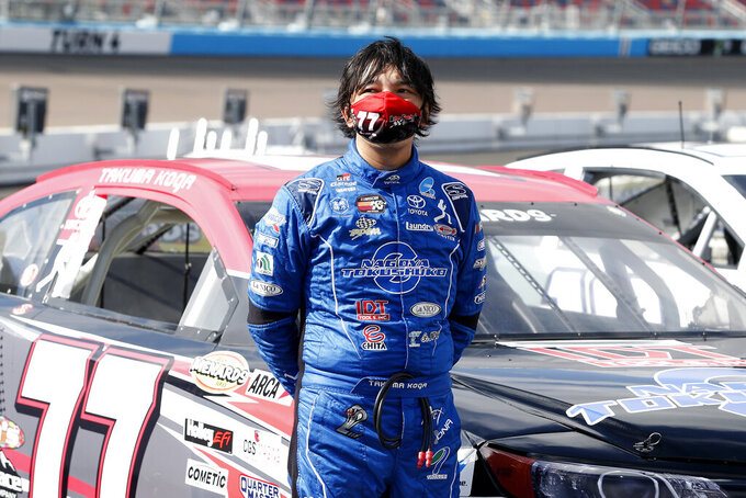 Takuma Koga, of Japan, stands next to his race car on pit road prior to an ARCA Series auto race at Phoenix Raceway, Saturday, Nov. 7, 2020, in Avondale, Ariz. (AP Photo/Ralph Freso)