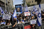 Israeli right wing activists hold flags and signs in support of Prime Minister Benjamin Netanyahu during a demonstration outside the Jerusalem district court In Jerusalem, Sunday, May 24, 2020. Israeli Prime Minister Benjamin Netanyahu was heading to court Sunday to face corruption charges in the first criminal trial ever against a sitting Israeli leader. Hebrew reads: