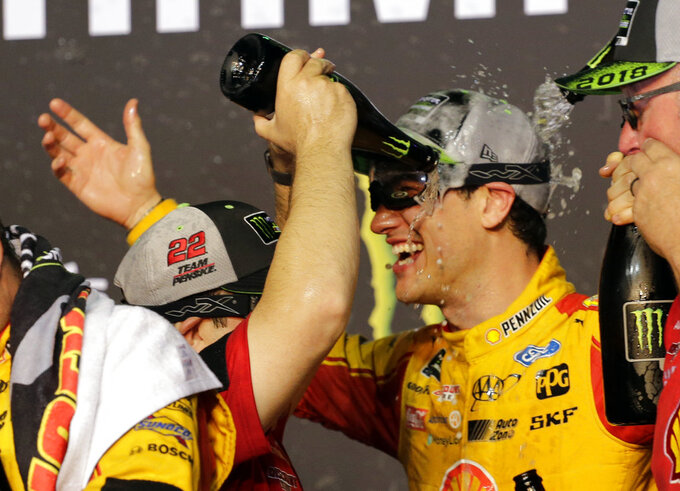 Joey Logano celebrates with champagne after winning the NASCAR Cup Series Championship auto race at the Homestead-Miami Speedway, Sunday, Nov. 18, 2018, in Homestead, Fla. (AP Photo/Terry Renna)