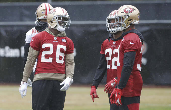 San Francisco 49ers running back Tevin Coleman (26) smiles next to Matt Breida (22) and Raheem Mostert during practice at the team's NFL football training facility in Santa Clara, Calif., Thursday, Jan. 16, 2020. The 49ers are scheduled to host the Green Bay Packers in the NFC Championship game Sunday. (AP Photo/Jeff Chiu)