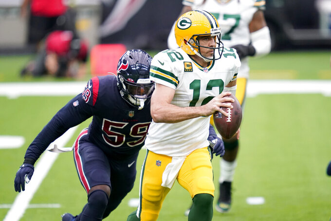 Green Bay Packers quarterback Aaron Rodgers (12) scrambles away from Houston Texans linebacker Whitney Mercilus (59) during the first half of an NFL football game Sunday, Oct. 25, 2020, in Houston. (AP Photo/Sam Craft)