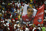 Fans hold a giant photo of Gedson Santos, a teenaged soccer player who was killed in a fire at the Flamengo training center last Friday, at Maracana Stadium in Rio de Janeiro, Brazil, Thursday, Feb. 14, 2019, ahead of a soccer match between Flamengo and Fluminense. (AP Photo/Leo Correa)