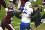 Mississippi State offensive lineman LaQuinston Sharp (63) shoves Tulsa offensive lineman Gabe Cantu (50) while a Tulsa staff member attempts to pull them apart during a postgame fight after Mississippi State's win in the Armed Forces Bowl NCAA college football game in Fort Worth, Texas, Thursday, Dec. 31, 2020. (Ian Maule/Tulsa World via AP)