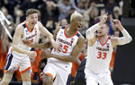 FILE - In this March 30, 2019, file photo, Virginia's Mamadi Diakite, center, reacts with teammates Kyle Guy and Jack Salt (33) after hitting a shot against Purdue to send the game into overtime in a regional final of the NCAA college basketball tournament in Louisville, Ky. (AP Photo/Michael Conroy, File)