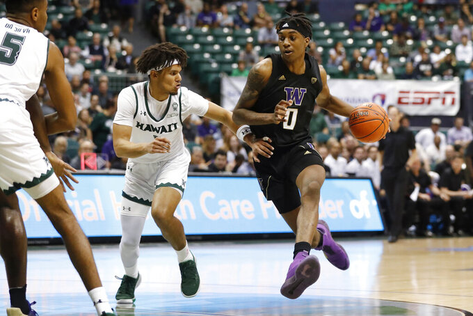 Hawaii guard Drew Buggs (1) defends against Washington forward Jayden McDaniels (0) during the first half of an NCAA college basketball game Monday, Dec. 23, 2019, in Honolulu. (AP Photo/Marco Garcia)
