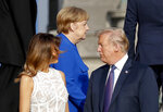 President Donald Trump, right, talks with first lady Melania Trump, left, as German Chancellor Angela Merkel, center, walks behind them after joining other heads of state and their spouses for a family photo at the Parc du Cinquantenaire in Brussels, Belgium, Wednesday, July 11, 2018. (AP Photo/Pablo Martinez Monsivais)