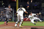 Pittsburgh Pirates relief pitcher Kyle Crick, right, tosses to catcher Elias Diaz (32) after fielding a ball hit by Arizona Diamondbacks' Blake Swihart as Wilmer Flores (41) scores from third on the play during the seventh inning of a baseball game in Pittsburgh, Monday, April 22, 2019. (AP Photo/Gene J. Puskar)