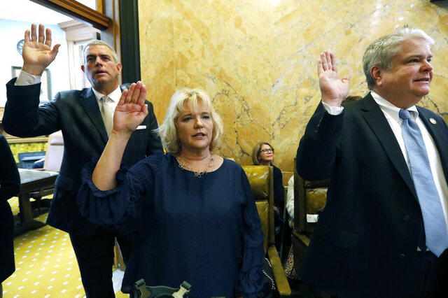 Speaker Philip Gunn, R-Clinton, left, Rep. Becky Currie, R-Brookhaven, center Rep. Steve Hopkins, R-Southaven, repeat the oath of office as they are sworn into office in the Mississippi House chambers at the Capitol in Jackson, Miss. (AP Photo/Rogelio V. Solis)