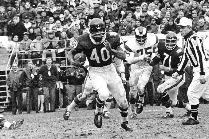 "FILE - In this Oct. 27, 1969, file photo, Chicago Bears running back Gale Sayers (40) runs for a 28-yard gain against the Los Angeles Rams, in Chicago, Ill. Hall of Famer Gale Sayers, who made his mark as one of the NFL's best all-purpose running backs and was later celebrated for his enduring friendship with a Chicago Bears teammate with cancer, has died. He was 77. Nicknamed ""The Kansas Comet"" and considered among the best open-field runners the game has ever seen, Sayers died Wednesday, Sept. 23, 2020, according to the Pro Football Hall of Fame. (AP Photo/File)"