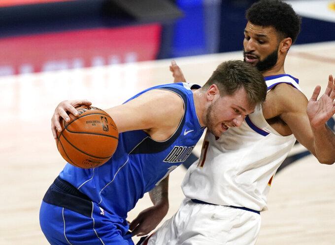Dallas Mavericks guard Luka Doncic, left, runs into Denver Nuggets guard Jamal Murray during the first half of an NBA basketball game Saturday, March 13, 2021, in Denver. (AP Photo/David Zalubowski)