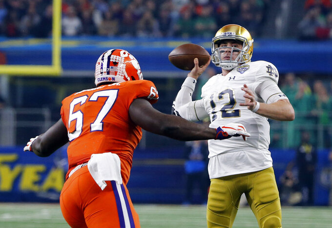 Clemson defensive tackle Albert Huggins (67) rushes as Notre Dame quarterback Ian Book (12) throws a pass in the first half of the NCAA Cotton Bowl semi-final playoff football game, Saturday, Dec. 29, 2018, in Arlington, Texas. (AP Photo/Michael Ainsworth)