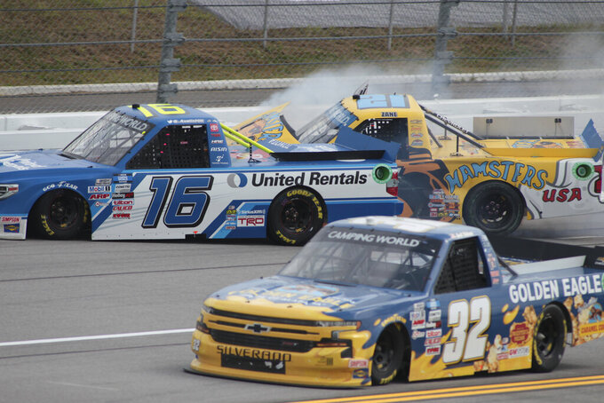 Austin Hill (16) and Zane Smith hit the wall during a NASCAR Truck Series auto race Saturday, Oct. 2, 2021, in Talladega, Ala. (AP Photo/Gre McWilliams )