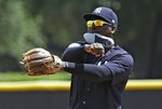 New York Yankees' Didi Gregorius carries the insert of his shoe in his mouth as he warms up before during a Gulf Coast League baseball game Monday, May 20, 2019, in Tampa, Fla. Gregorius is playing for the first time since having Tommy John surgery. (AP Photo/Chris O'Meara)