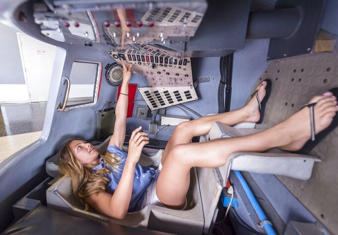 FILE- Tara Clemenceau, 11, visiting from France, tries her hand at the controls of a Mercury space capsule at the U.S. Space & Rocket Center in Huntsville, Ala in this July 12, 2018 file photo. Space Camp, an educational program attended by nearly 1 million people, including a dozen who went on to become astronauts or cosmonauts, said Tuesday, July 28, 2020 it's in danger of closing without a cash infusion because of the coronavirus pandemic. (AP Photo/Vasha Hunt, File)