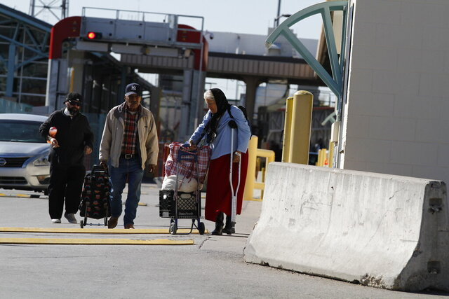Silvia Shadden, 68, in blue, pulls a cart as she leaves a U.S. customs checkpoint in El Paso, Texas after a she went to Ciudad Juarez, Mexico for a doctor's appointment on Friday, March 20, 2020. Shadden, of El Paso, says she needs a weekly vitamin injection to prevent muscle atrophy. Her medicine costs $10 in Ciudad Juarez and $70 in El Paso. She walks more than a mile to get the treatment. She fears that the border may close and she won't be able to afford medicine in the U.S. (AP Photo/Cedar Attanasio)