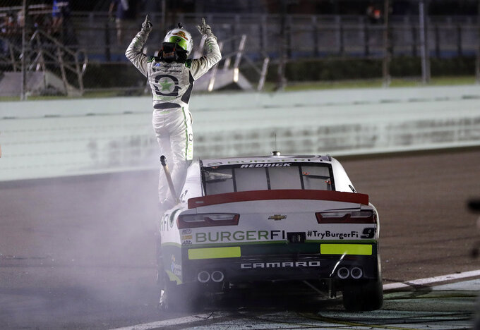 Tyler Reddick stands on his car after winning the NASCAR Xfinity Series championship auto race at the Homestead-Miami Speedway, Saturday, Nov. 17, 2018, in Homestead, Fla. (AP Photo/Lynne Sladky)